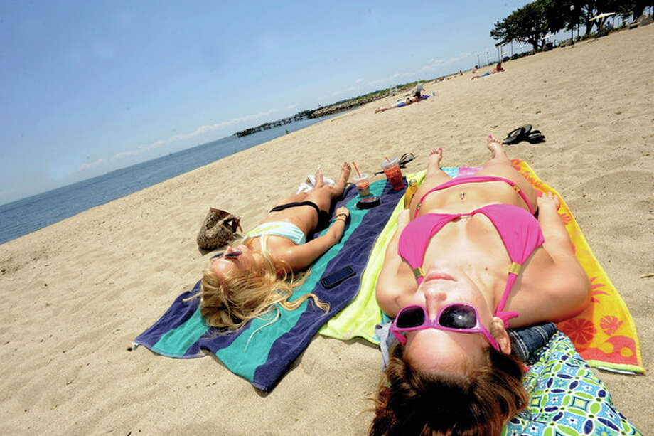 Dana Karp and Chloe Fosella take in the sun Monday afternoon at Calf Pasture beach. hour photo/matthew vinci / (C)2011, The Hour Newspapers, all rights reserved