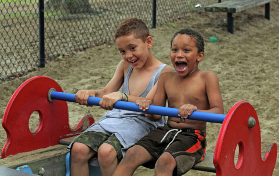 Pedro Figeuroa, 8, and Xavier Felice, 6, have fun on the seesaw at Calf Pasture Beach in Norwalk Sunday afternoon despite the rain. Hour Photo / Danielle Robinson