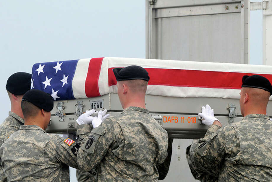 An Army carry team lifts a transfer case containing the remains of Staff Sgt. Richard L. Berry Tuesday, July 24, 2012 at Dover Air Force Base, Del. According to the Department of Defense, Berry, 27, of Scottsdale, Ariz., died July 22, 2012 in Kandahar, Afghanistan of wounds from an improvised explosive device. (AP Photo/Steve Ruark) / FR96543 AP