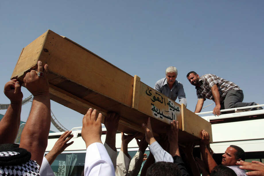 Family members of Khalaf Mohsen, 38, load his coffin onto a vehicle before burial in the Shiite holy city of Najaf, 100 miles (160 kilometers) south of Baghdad, Iraq, Tuesday, July 24, 2012. The man was killed when violence shook more than a dozen Iraqi cities Monday, killing more than 100 people in coordinated bombings and shootings and wounding twice as many in the country's deadliest day in more than two years. (AP Photo/Alaa al-Marjani) / AP