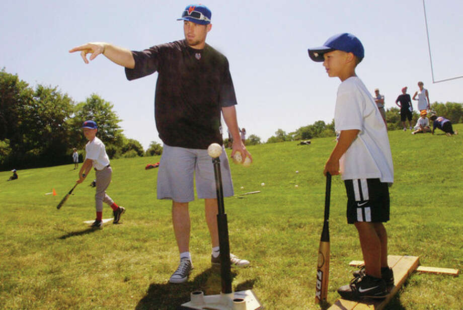 Hour photo/Erik Trautmann Daniel Murphy of the New York Mets offers some pointers to 6-year-old Will Singewald of Norwalk during the Baseball World summer camp in Westport on Friday. / (C)2011, The Hour Newspapers, all rights reserved