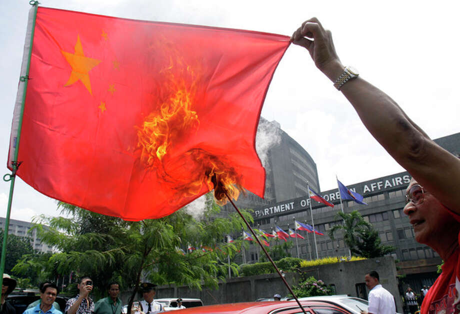 Former police officer Abner Afuang burns a Chinese flag in front of the Department of Foreign Affairs to oppose the presence of Chinese vessels in the disputed territory in the South China Sea Friday, July 27, 2012 in suburban Pasay City, south of Manila, Philippines. Afuang called on the government to persist on its claim on Scarborough Shoal which is within the country's economic zone. (AP Photo/Photo/Pat Roque) / AP