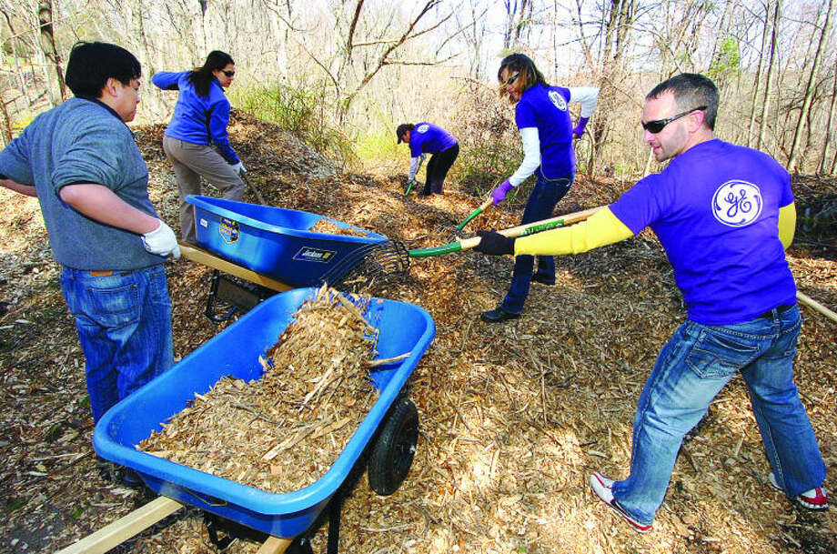 Volunteers from GE Capitol load wood chips into wheelbarrows for work on Pathways at Woodcock Nature Center in Wilton on Earth Day.