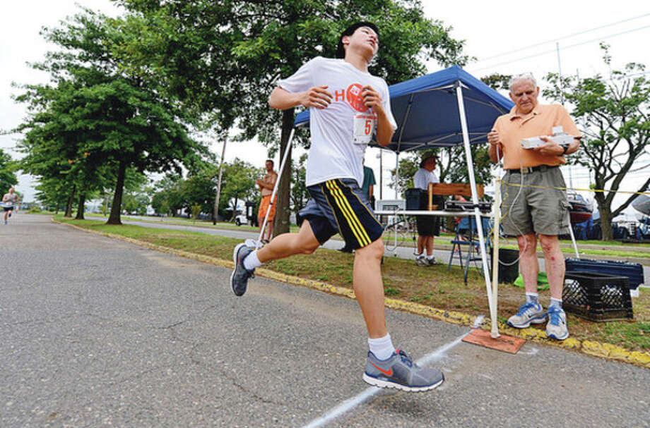 Colin Lu comes in first place at the 14th Annual Ian James Eaccarino Memorial 9-Mile Race at Calf Pasture Beach Saturday.Hour photo / Erik Trautmann / (C)2012, The Hour Newspapers, all rights reserved