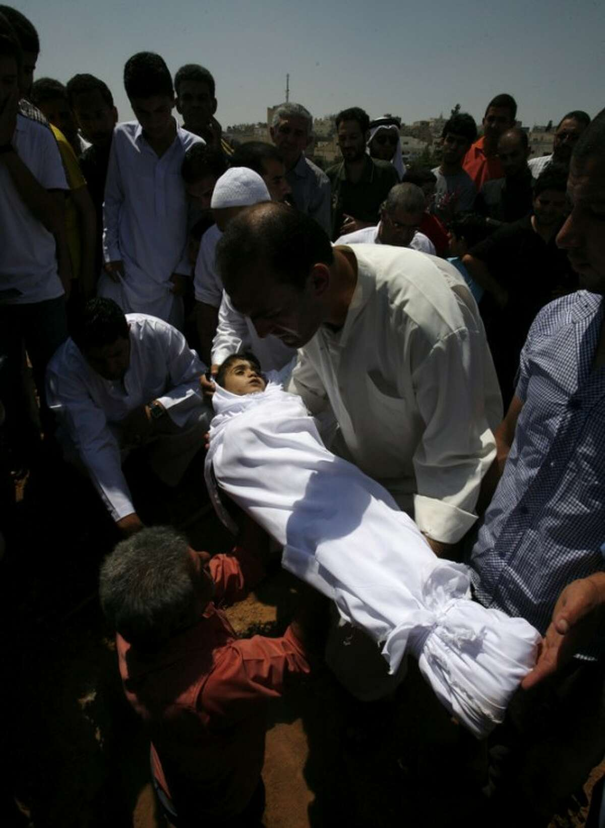 A relative holds the body of a six year old Syrian boy Bilal El-Lababidi during his funeral in Ramtha, Jordan, Friday July 27, 2012. The boy was shot dead by Syrian army as his parents and a dozen other refugees tried to cross a border to seek refuge in Jordan, his mother said. (AP Photo/Mohammad Hannon)