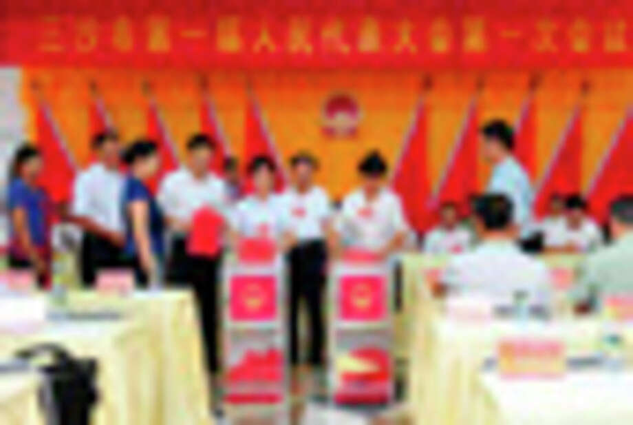 In this photo released by China's Xinhua News Agency, representatives cast their votes in the first session of the first Sansha Municipal People's Congress held on Yongxing Island, the government seat of Sansha City in south China's Hainan province Monday, July 23, 2012. China has rolled out the red carpet for its newest city, on a small, remote island in the South China Sea that is also claimed by Vietnam. Beijing on Tuesday, July 24, formally established the city of Sansha to bolster its claim on the sea's oil and gas-rich waters. The move is likely to anger China's neighbors and competing claimants in a dispute that has at times led to maritime standoffs. (AP Photo/Xinhua, Hou Jiansen) NO SALES / Xinhua News Agency