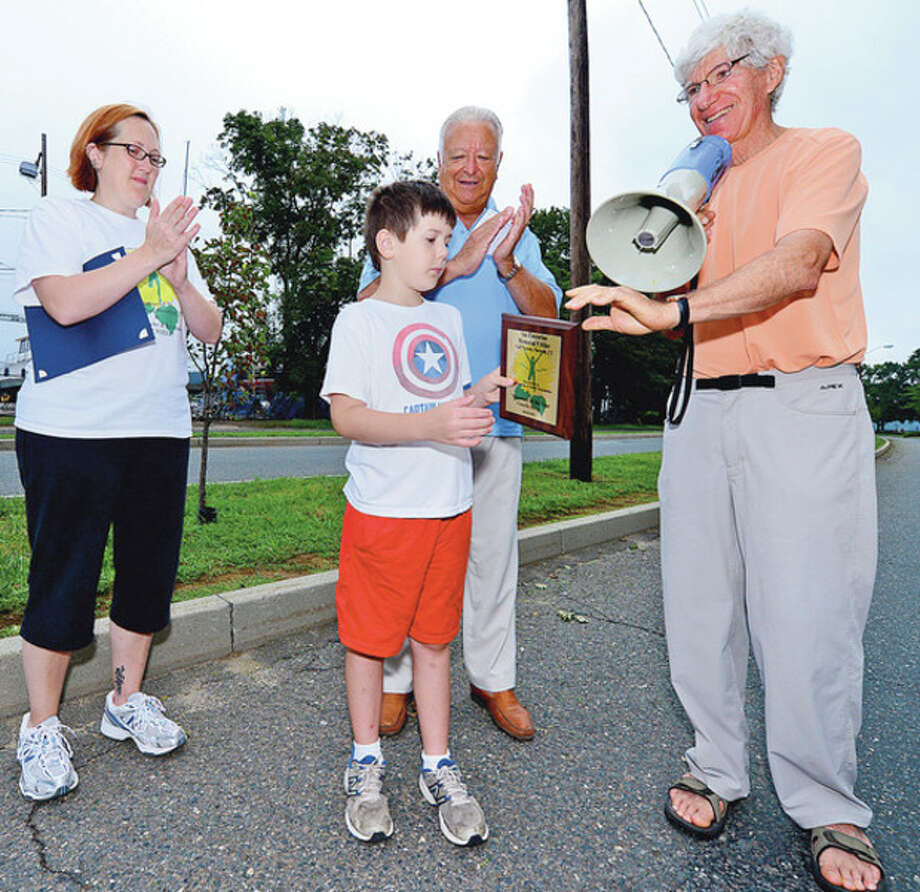 Charlie Doyle receives recognition for volunteering at the Ian James Eaccarino Memorial 9-Mile Race at Calf Pasture Beach while his mom paige Doyle, mayor Richard Moccia and Larry Katz look on Saturday.Hour photo / Erik Trautmann / (C)2012, The Hour Newspapers, all rights reserved