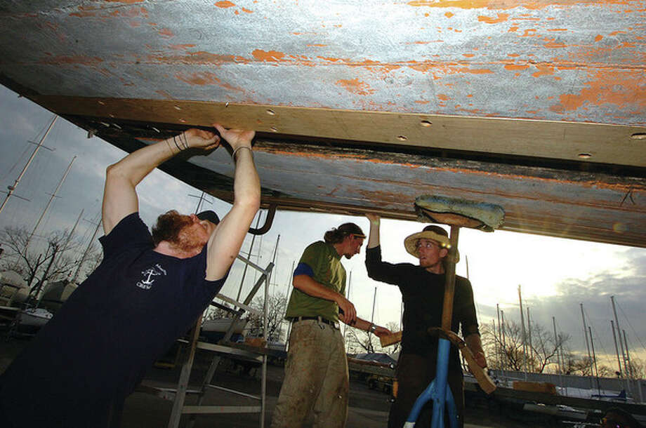 Hour Photo/ Alex von Kleydorff. Captain Nick Rogers fits a template for a new plank near the stern of the Clearwater. / 2011 The Hour Newspapers
