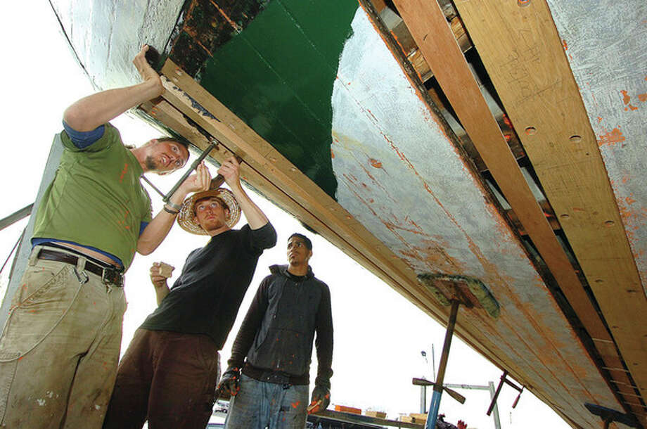 From left, Second Mate Parks Marion, Deckhand Chris O'Reilly and Bo'sun Carlos Duran works at fitting a new plank in the hull of the sloop Clearwater. / 2011 The Hour Newspapers