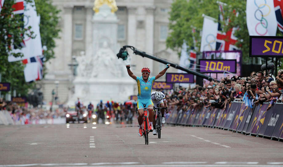 Kazakhstan's Alexandr Vinokourov celebrates as he crosses the finish line to win the Men's Road Cycling race at the 2012 Summer Olympics, Saturday, July 28, 2012, in London. Rigoberto Uran of Colombia took silver, with Alexander Kristoff of Norway claiming bronze. (AP Photo/Christophe Ena) / AP