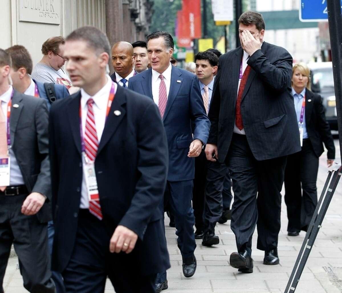 Avoiding a traffic jam, Republican presidential candidate, former Massachusetts Gov. Mitt Romney walks down Grosvenor Place in London to meet Ireland's Prime Minister Enda Kenny at the Embassy of Ireland in London, Friday, July 27, 2012. (AP Photo/Charles Dharapak)