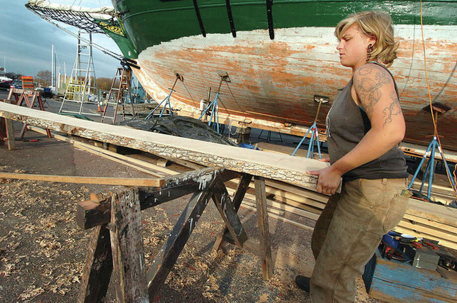 Hour Photo/ Alex von Kleydorff. Ships engineer Chelsea Fisher helps move at one end, a board of White Oak for cutting into planks for Clearwater. / 2011 The Hour Newspapers