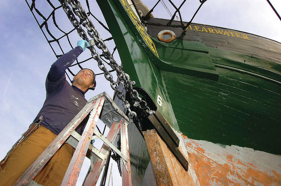 Hour photos / Alex von Kleydorff Above, apprentice Josh Scornavacci puts a coat of marine paint on the bob chain at the bow of the sloop Clearwater at Cove Marina on Monday. Below, the stern of Clearwater. / 2011 The Hour Newspapers