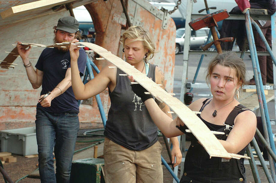 Hour photos / Alex von Kleydorff First Mate Aleythea Dolested, Engineer Chelsea Fisher and Captain Nick Rogers move a template for a replacement plank to the board from which they will cut it on the sloop Clearwater at Cove Marina on Monday. / 2011 The Hour Newspapers