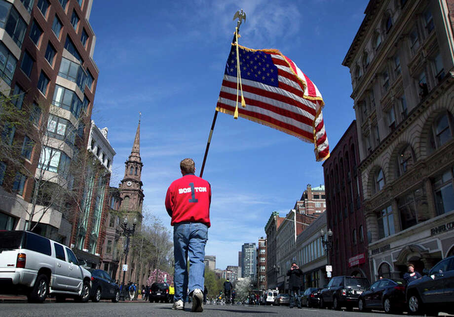 Lt. Mike Murphy of the Newton, Mass., fire dept., carries an American flag down the middle of Boylston Street after observing a moment of silence in honor of the victims of the bombing at the Boston Marathon near the race finish line, Monday, April 22, 2013, in Boston, Mass. At 2:50 p.m., exactly one week after the bombings, many bowed their heads and cried at the makeshift memorial on Boylston Street, three blocks from the site of the explosions, where bouquets of flowers, handwritten messages, and used running shoes were piled on the sidewalk. (AP Photo/Robert F. Bukaty) / AP