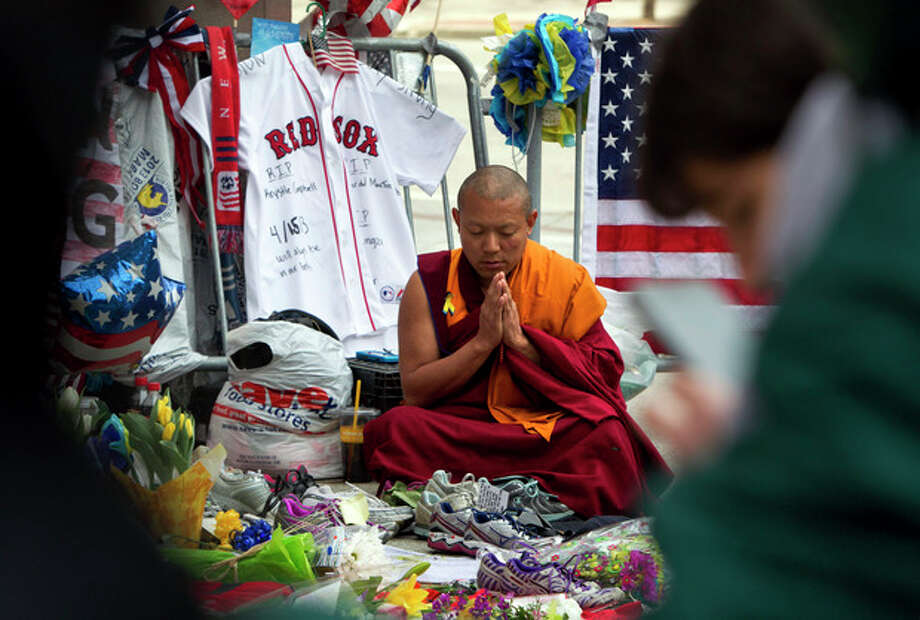A man prays at a memorial for the victims of the Boston Marathon bombing on Boylston Street near the race finish line, Monday, April 22, 2013, in Boston, Mass. At 2:50 p.m., exactly one week after the bombings, many bowed their heads and cried at the makeshift memorial on Boylston Street, three blocks from the site of the explosions, where bouquets of flowers, handwritten messages, and used running shoes were piled on the sidewalk. (AP Photo/Robert F. Bukaty) / AP