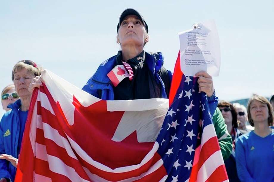 Ottawa runner Floralove Katz holds American and Canadian flags at Parliament Hill before a march to the United States Embassy in Ottowa in solidarity with the Boston community, in Ottawa on Monday, April 22, 2013. (AP Photo/The Canadian Press, Justin Tang) / The Canadian Press