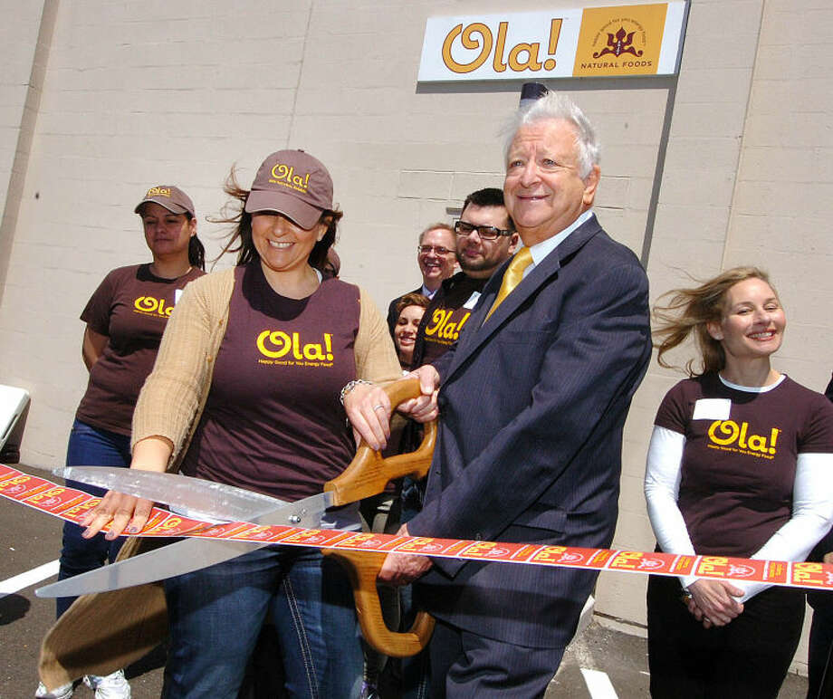 Hour Photo/Alex von Kleydorff . Mayor Richard Moccia and Ola Founder and President Dina Houser cut the ribbon at the Ola Natural Foods expanded facility in Norwalk