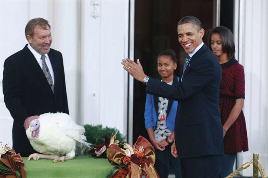 President Barack Obama, with daughters Sasha and Malia, pardons Liberty, a 19-week old, 45-pound turkey, on the occasion of Thanksgiving, Wednesday, Nov. 23, 2011, on the North Portico of the White House in Washington. At left is National Turkey Federation Chairman Richard Huisinga. (AP Photo/Charles Dharapak) / AP