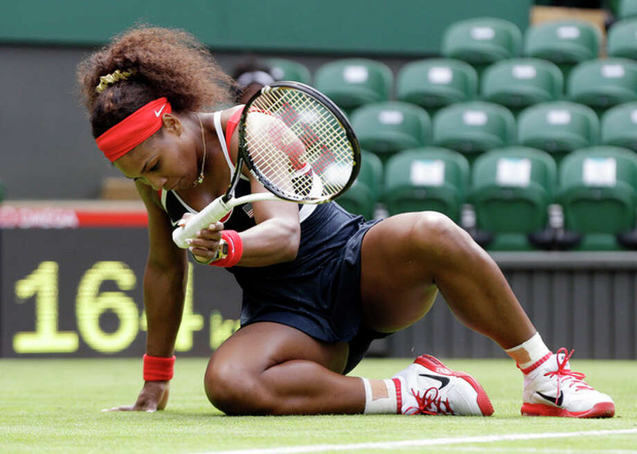 Serena Williams of the United States gets up after slipping on the grass against Jelena Jankovic of Serbia during a first round match at the All England Lawn Tennis Club in Wimbledon, London at the 2012 Summer Olympics, Saturday, July 28, 2012. (AP Photo/Elise Amendola) / AP
