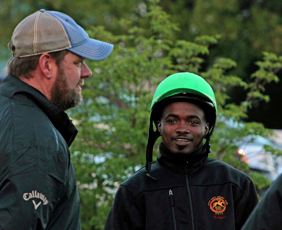 Jockey Kevin Krigger, right, talks with trainer Doug O'Neill, left, as they watch horses work out at Churchill Downs, Sunday, April 28, 2013, in Louisville, Ky. Krigger is to ride Kentucky Derby hopeful Goldencents for O'Neill in the race. (AP Photo/Garry Jones) / FR50389 AP