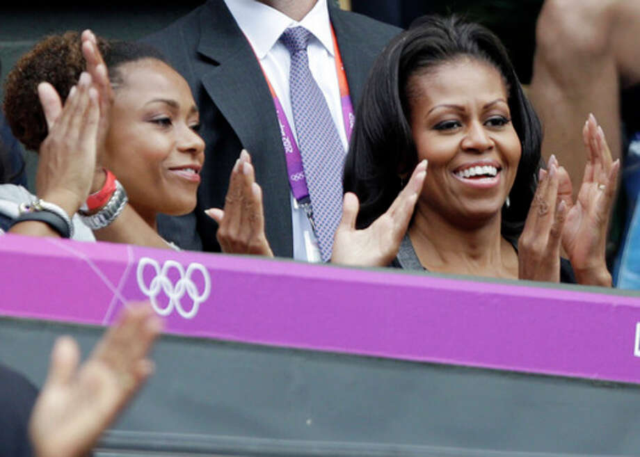 First lady Michelle Obama, right, applauds with former USA gymnast Dominique Dawes as they watch Serena Williams of the United States compete against Jelena Jankovic of Serbia at the All England Lawn Tennis Club in Wimbledon, London at the 2012 Summer Olympics, Saturday, July 28, 2012. (AP Photo/Elise Amendola) / AP