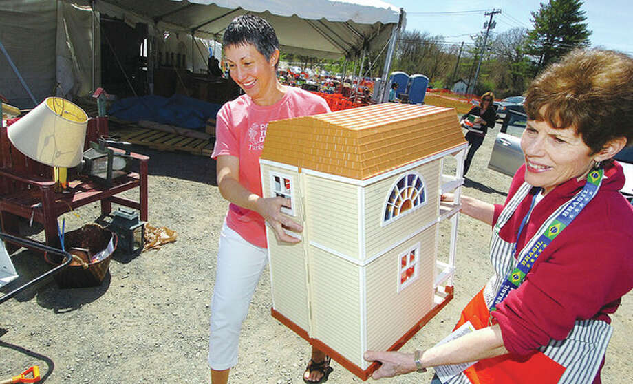 Hour Photo/Alex von Kleydorff Wiltons Jody Marcell has help from volunteer Jannie Stolting getting a play house to the donation area, just some of the items she is donating to Minks to Sinks sale this weekend in Wilton / 2013 The Hour Newspapers