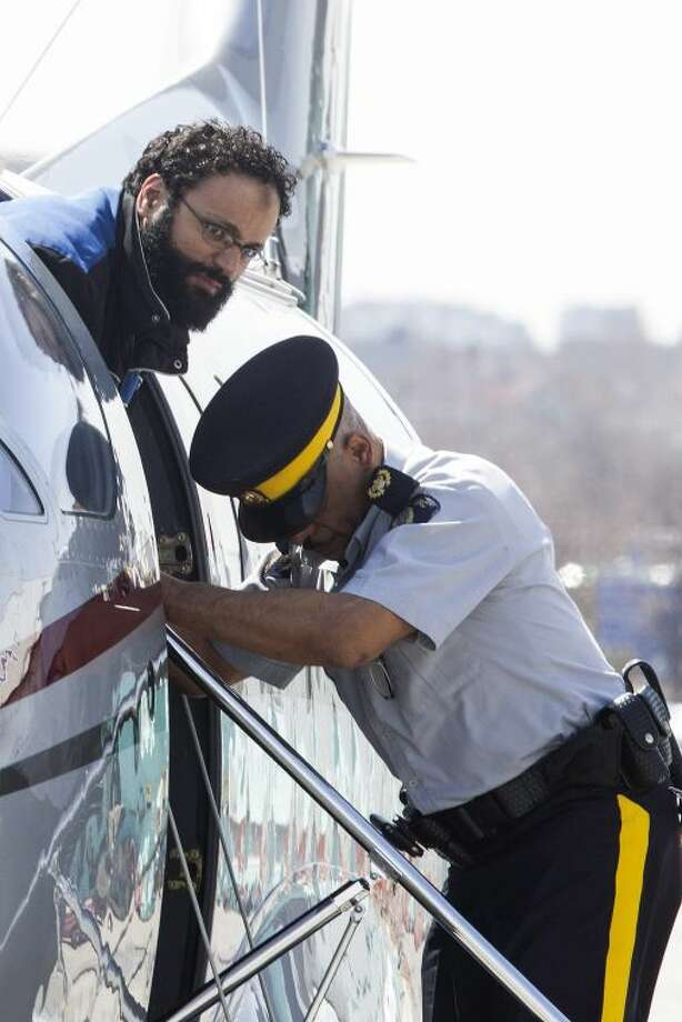 "Chiheb Esseghaier, one of two men accused of plotting a terror attack on rail target, is led off a plane by an Royal Canadian Mounted Police (RCMP) officer at Buttonville Airport just north of Toronto on Tuesday April 23, 2013. Canadian investigators say Raed Jaser, 35, and his suspected accomplice Esseghaier, 30, received ""directions and guidance"" from members of al-Qaida in Iran. In a brief court appearance in Montreal Tuesday, Esseghaier declined to be represented by a court-appointed lawyer. He made a brief statement in French in which he called the allegations against him unfair. (AP Photo/The Canadian Press, Chris Young)"