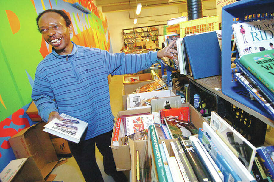 Hour Photo/Alex von Kleydorff . Ekpo Ekpo smiles as he goes through thousands of books and buys some 500 of them to send to schools in Nigeria and India. Ekpo has been coming to the Wilton Library's book sale bargain day when its 5 dollar bag 10 dollar box for books that didnt sell and through his church he ships the books to those in need of all ages / 2013 The Hour Newspapers