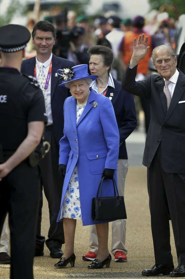 Britain's Queen Elizabeth II arrives to visit the Orbit Tower, accompanied by Prince Phillip the Duke of Edinburgh, right, Princess Anne, above-center, and her husband Tim Laurence, center-left, in the Olympic Park at the 2012 Summer Olympics, Saturday, July 28, 2012, in London. (AP Photo/Ben Curtis)
