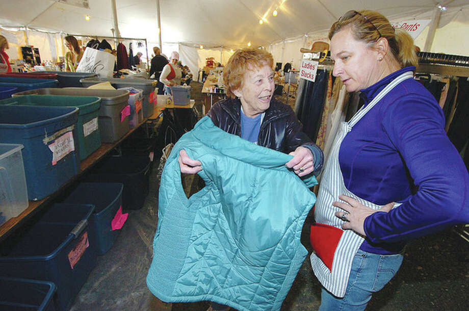 Hour Photo/Alex von Kleydorff Mary Lou Logan and Nancy Budd sort some of the clothing in the womens area as volunteers help organize and price donated and consigned goods for Minks to Sinks sale in Wilton this weekend / 2013 The Hour Newspapers