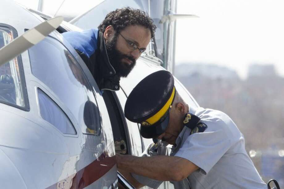 """Chiheb Esseghaier, one of two men accused of plotting a terror attack on rail target, is led off a plane by an Royal Canadian Mounted Police (RCMP) officer at Buttonville Airport just north of Toronto on Tuesday April 23, 2013. Canadian investigators say Raed Jaser, 35, and his suspected accomplice Esseghaier, 30, received """"directions and guidance"""" from members of al-Qaida in Iran. In a brief court appearance in Montreal Tuesday, Esseghaier declined to be represented by a court-appointed lawyer. He made a brief statement in French in which he called the allegations against him unfair. (AP Photo/The Canadian Press, Chris Young)"""