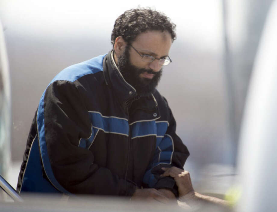 """Chiheb Esseghaier, one of two suspects accused of plotting with al-Qaida in Iran to derail a train in Canada, arrives at Buttonville Airport just north of Toronto, on Tuesday, April 23, 2013. Canadian investigators say Raed Jaser, 35, and his suspected accomplice Esseghaier, 30, received """"directions and guidance"""" from members of al-Qaida in Iran. In a brief court appearance in Montreal Tuesday, Esseghaier declined to be represented by a court-appointed lawyer. He made a brief statement in French in which he called the allegations against him unfair. (AP Photo/The Canadian Press, Frank Gunn)"""