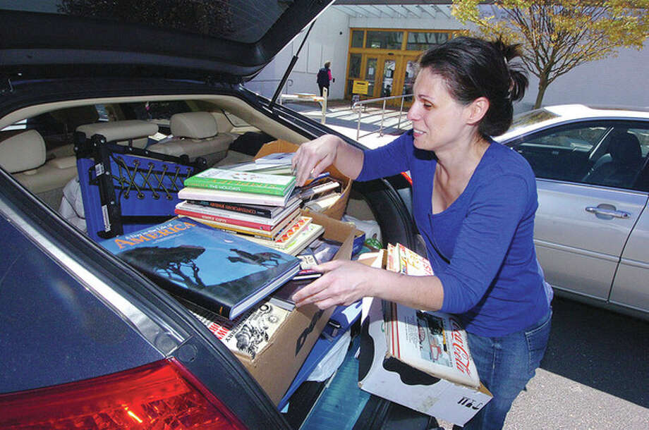 Hour Photo/Alex von Kleydorff Margot Levy fills her car to the top with bargain books on the last day of the Wilton Library's book sale / 2013 The Hour Newspapers