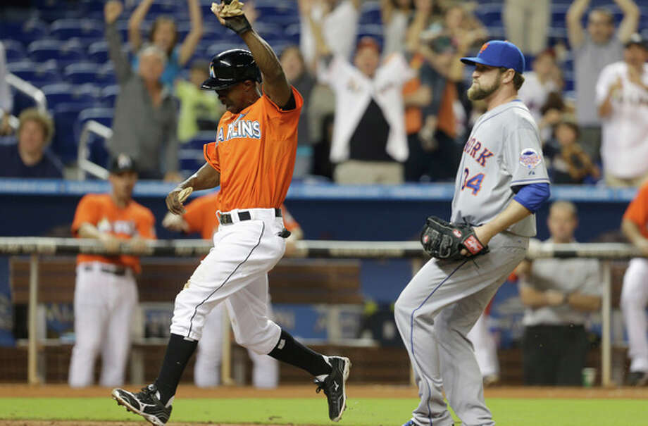 Miami Marlins' Juan Pierre, left, scores the game-winning run on a wild pitch by New York Mets relief pitcher Brandon Lyon (34) in the ninth inning during a baseball game, Tuesday, April 30, 2013, in Miami. The Marlins defeated the Mets 2-1. (AP Photo/Lynne Sladky) / AP