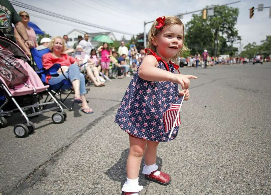 Finley Pennoyer, 2, enjoys her first parade during Norwalk''s annual Memorial Day Parade Monday morning. Hour Photo / Danielle Robinson