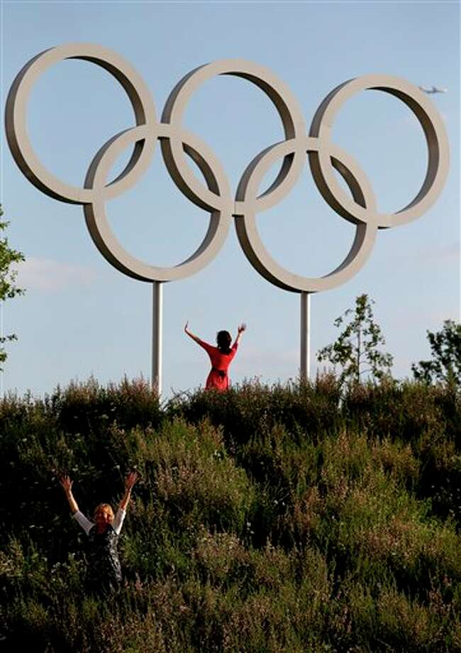 Mandy Burrell, bottom left, poses near the Olympic rings at the Olympic Park during the 2012 Summer Olympics, Saturday, July 28, 2012, in London. (AP Photo/Jae C. Hong) / AP