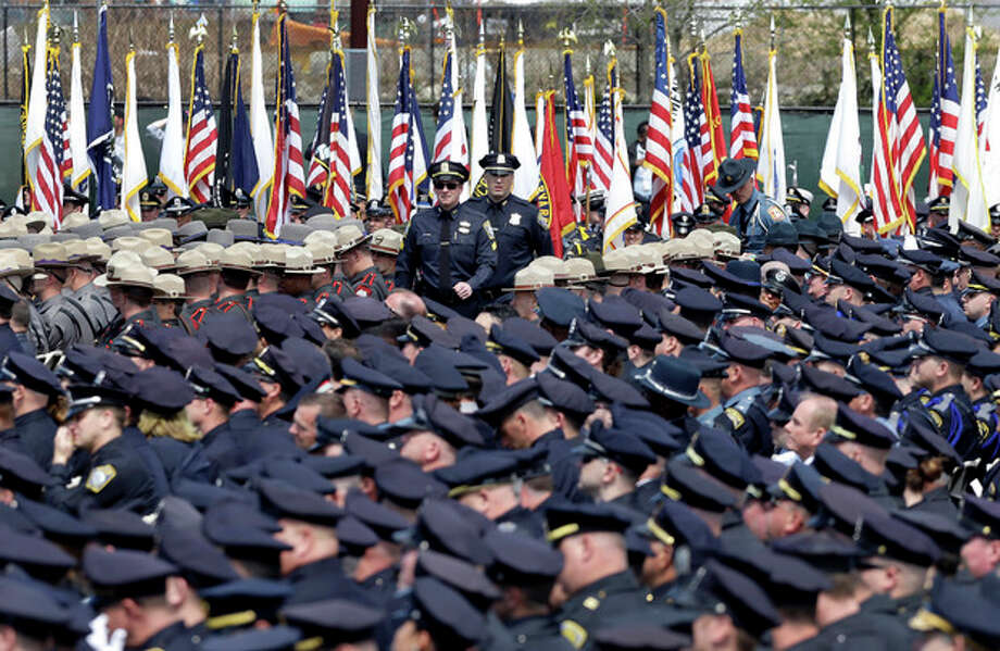 Police officers arrive to a memorial service for fallen Massachusetts Institute of Technology campus officer Sean Collier at MIT in Cambridge, Mass. Wednesday, April 24, 2013. Authorities say Collier was killed by the Boston Marathon bombing suspects last Thursday, April 18. He had worked for the department a little more than a year. (AP Photo/Elise Amendola) / AP