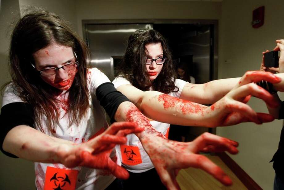"Students Shara Evans, of West Bloomfield, Mich., left, and Maia Frieser, of New York, act during a ""zombie apocalypse"" exercise, which included students dressing up as the undead, in Ann Arbor, Mich. Tuesday April 23, 2013. The exercise was designed to get School of Public Health students thinking about what the appropriate response should be during a disaster. (AP Photo/Paul Sancya) / AP"