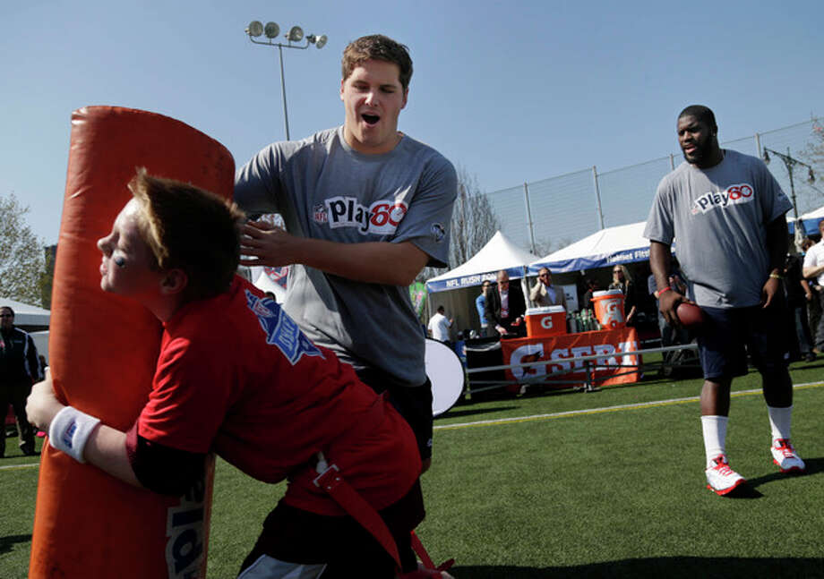 NFL draft prospects Luke Joeckel of Texas A&M, rear left, and Menelik Watson of Florida State, right, participate in a youth football clinic in New York, Wednesday, April 24, 2013. The draft begins Thursday in New York. (AP Photo/Seth Wenig) / AP