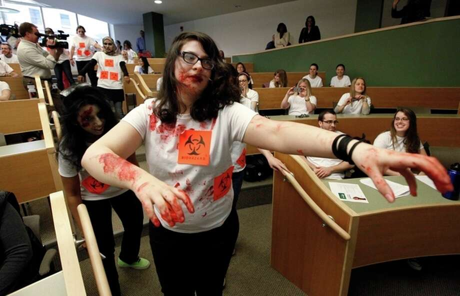 "Maia Frieser, of New York, acts during a ""zombie apocalypse"" exercise, which included students dressing up as the undead, on the University of Michigan campus in Ann Arbor, Mich. Tuesday April 23, 2013. The exercise was designed to get School of Public Health students thinking about what the appropriate response should be during a disaster. (AP Photo/Paul Sancya) / AP"