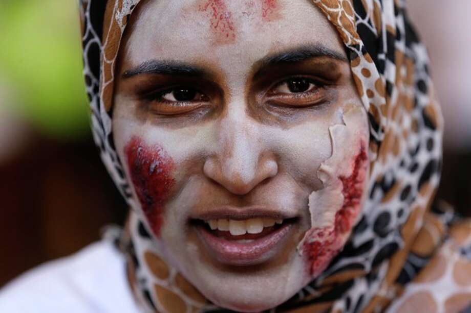 """Amena Qureshi, of Flint, Mich., wears makeup during a """"zombie apocalypse"""" exercise, which included students dressing up as the undead, on the University of Michigan campus in Ann Arbor, Mich. Tuesday April 23, 2013. The exercise was designed to get School of Public Health students thinking about what the appropriate response should be during a disaster. (AP Photo/Paul Sancya) / AP"""