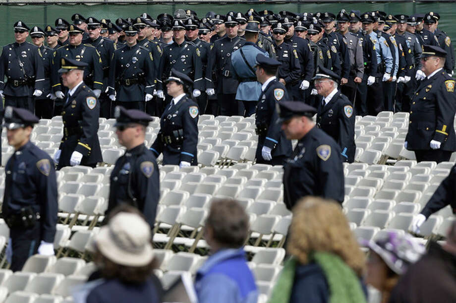 Police officers and civilians arrive to a memorial service for fallen Massachusetts Institute of Technology campus officer Sean Collier at MIT in Cambridge, Mass. Wednesday, April 24, 2013. Authorities say Collier was killed by the Boston Marathon bombing suspects last Thursday. He had worked for the department a little more than a year. (AP Photo/Elise Amendola) / AP