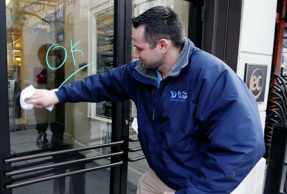 Antonio DaSilva, of Woburn, Mass., cleans a mark made on the entrance to a building on Boylston Street in Boston, Wednesday, April 24, 2013. Businesses opened and traffic was allowed to flow all the way down Boylston Street on Wednesday morning for the first time since two explosions at the Boston Marathon on April 15. (AP Photo/Michael Dwyer) / AP