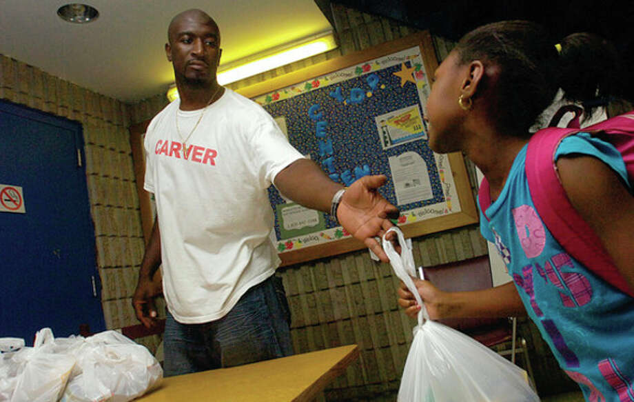Hour Photo / Erik Trautmann Above, George Washington Carver Community Center staffer Timothy Williams hands out bags of food from the Summer KIÕ's Backpack Program to campers at the center on Friday afternoon. The program to feed needy kids on the weekend came from the Connecticut Food Bank in conjuction with the Norwalk Children Foundation, Pepperidge Farm, , the United Way and GE. / (C)2011, The Hour Newspapers, all rights reserved