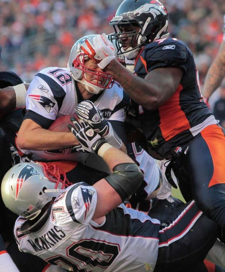 New England Patriots quarterback Tom Brady (12) pushes up against Denver Broncos defensive end Robert Ayers (91) for a 1-yard touchdown run in the second quarter of an NFL football game, Sunday, Dec. 18, 2011, in Denver. (AP Photo/Barry Gutierrez) / /