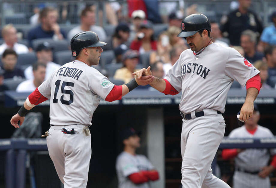 Boston Red Sox's Dustin Pedroia, left, and Adrian Gonzalez celebrate after scoring on a double by Will Middlebrooks during the first inning of the baseball game against the New York Yankees at Yankee Stadium in New York, Saturday, July 28, 2012. (AP Photo/Seth Wenig) / AP