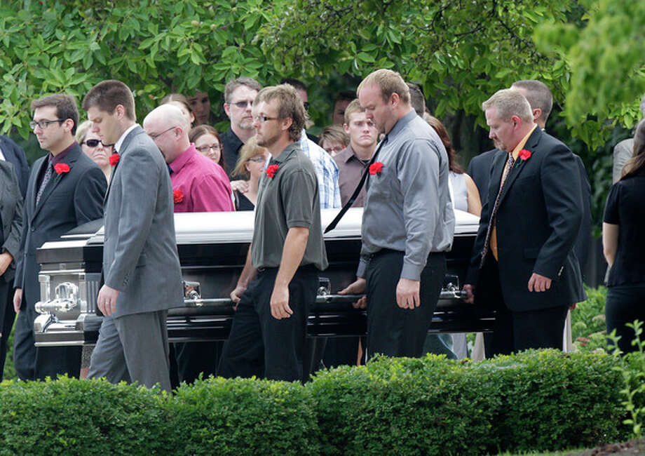 """Pallbearers carry Matt McQuinn, killed in the Aurora, Colorado movie theater shooting, from the church after his funeral Saturday, July 28, 2012, in Springfield, Ohio. McQuinn shielded his girlfriend, Samantha Yowler, from gunfire during the shooting. Twelve people were killed and dozens were wounded in a shooting attack last Friday at a packed movie theater during a showing of the Batman movie, """"The Dark Knight Rises."""" Police have identified the suspected shooter as James Holmes, 24. (AP Photo/Jay LaPrete) / FR52593 AP"""