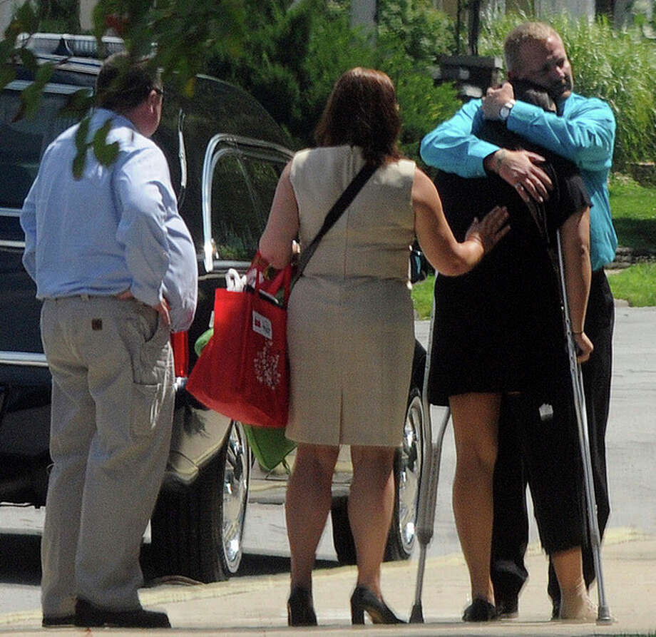 Samantha Yowler, right, is comforted by relatives Friday, July 27, 2012, at Maiden Lane Church of God in Springfield, Ohio. Yowler, a Graham High School graduate, was shot in the leg on Friday, July 20, in Aurora, Colo., as her boyfriend, Springfield native Matt McQuinn shielded her from the gunman. McQuinn was one of 12 who died in the shooting, which injured 58. (AP Photo/Springfield News-Sun, Marshall Gorby) / Springfield News-Sun