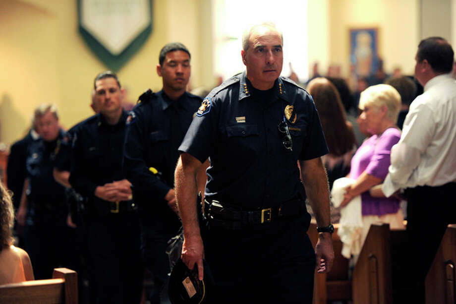 """Aurora Police Chief Dan Oates, right, walks with other law enforcement officers as they attend the funeral for Aurora, Colo. movie theater shooting victim AJ Boik, Friday, July 27, 2012, at the Queen of Peace Catholic Church, in Aurora, Colo. Boik, 18, was one of twelve people killed in a shooting attack, that also wounded dozens, last Friday at a packed movie theater during a showing of the Batman movie, """"The Dark Knight Rises."""" Police have identified the suspected shooter as James Holmes, 24. (AP Photo/Denver Post, Joe Amon, Pool) / Pool Denver Post"""
